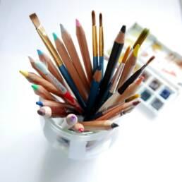 Een pot met gekleurde potloden en penselen zoals gebruikt door een creatieve designer